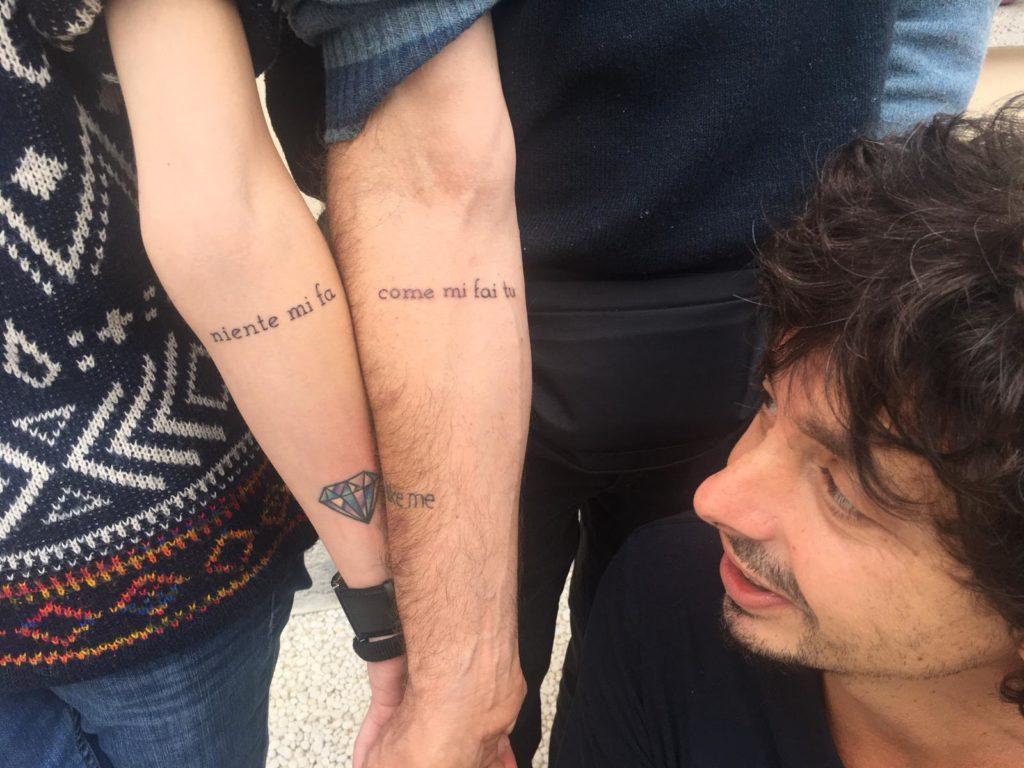 Riccardo Sinigallia guarda il tatuaggio di Marco e Laura