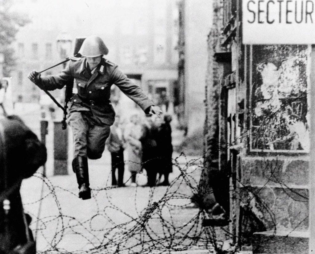 Conrad Schumann salta sopra il filo spinato raggiungendo la Germania Ovest. Berlino, 15 agosto 1961. Fotografia di Peter Leibing